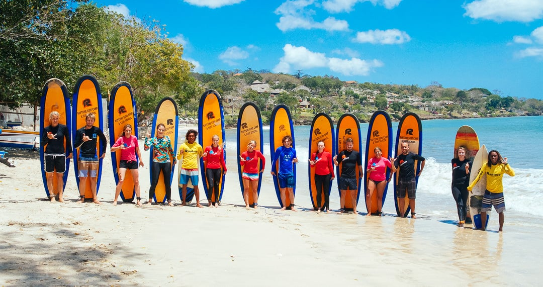 A group of surfer girls in the beach having surf lessons