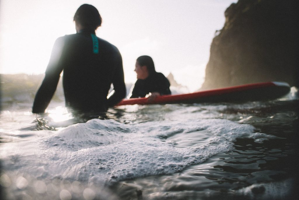 A surf instructor helping a beginner surfer