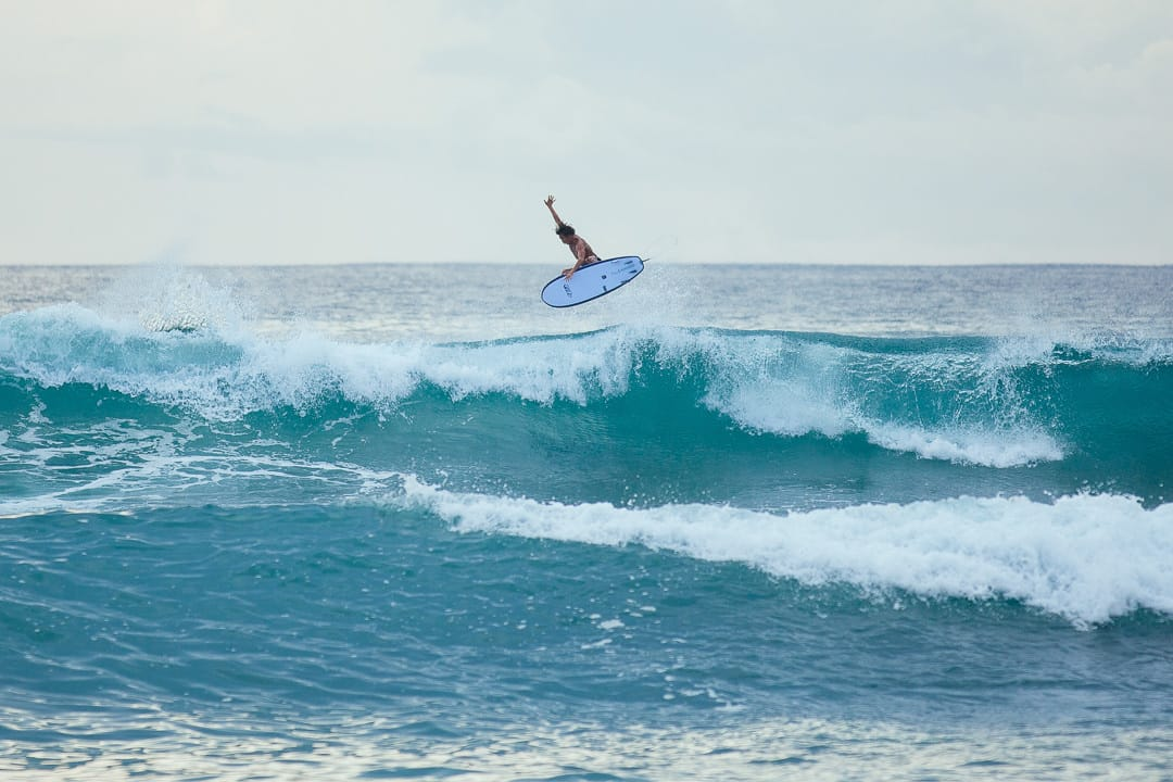 A surfer flying from a wave in Bali Canggu
