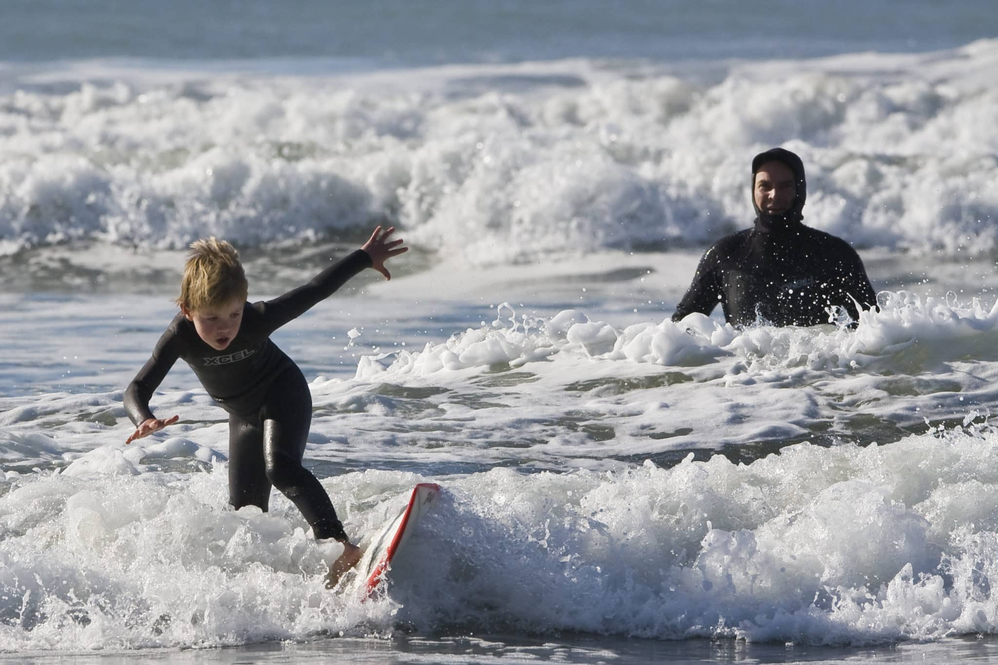 Father teaching his son how to surf